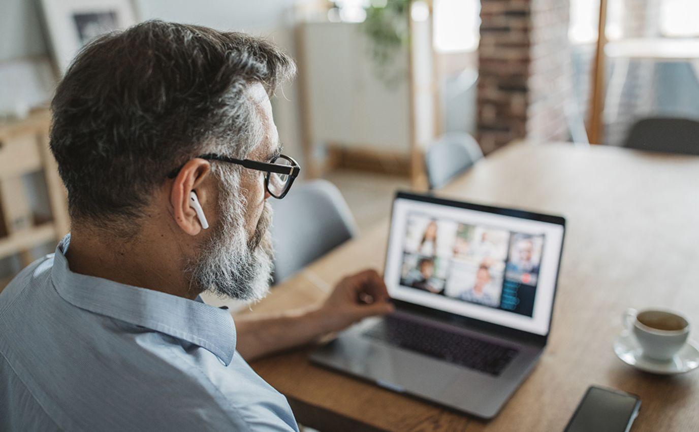 mann sitter med mac og jobber hjemmefra ved kjøkkenbord
