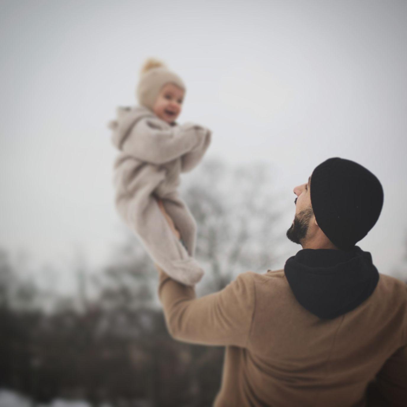 En vinterkledd mann står ute i snøen. Han løfter den lille datteren sin høyt over hodet, og datteren ler.