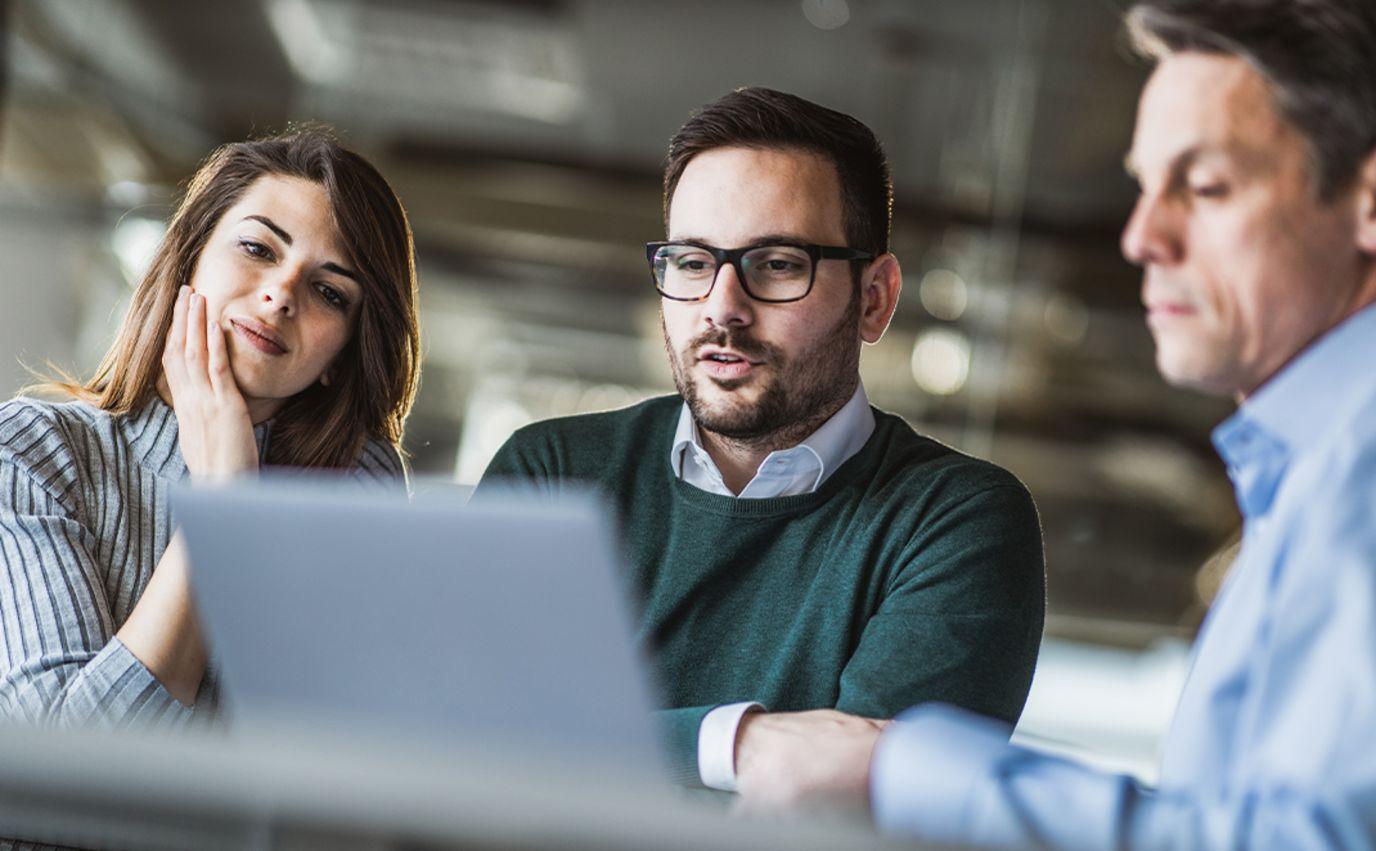 Mennesker foran datamaskin på jobb