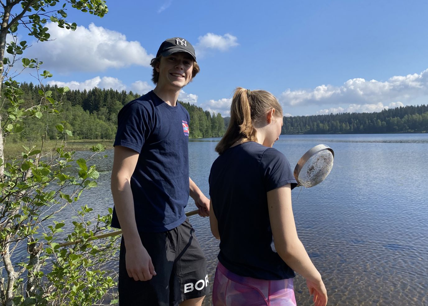 To glade elever med en hov foran et vann