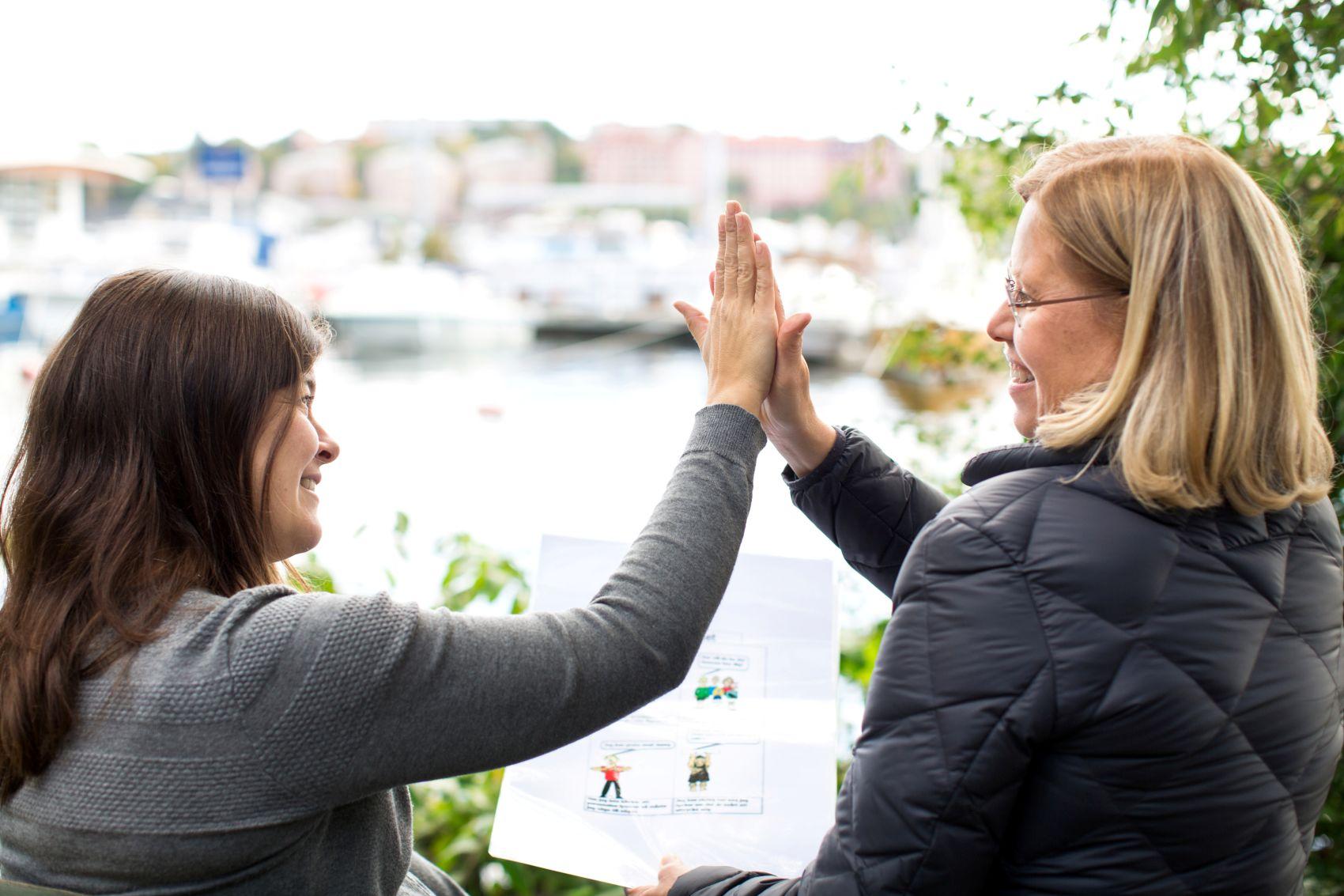 En glad kvinne og en miljøarbeider i Stendi gir hverandre en high five.