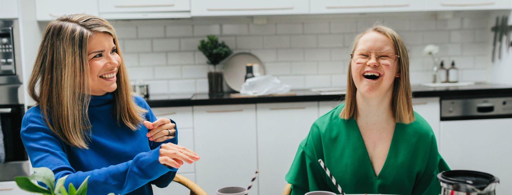 En voksen kvinne sitter ved kjøkkenbordet, ved siden av henne sitter det en jente med downsyndrom, hun smiler.