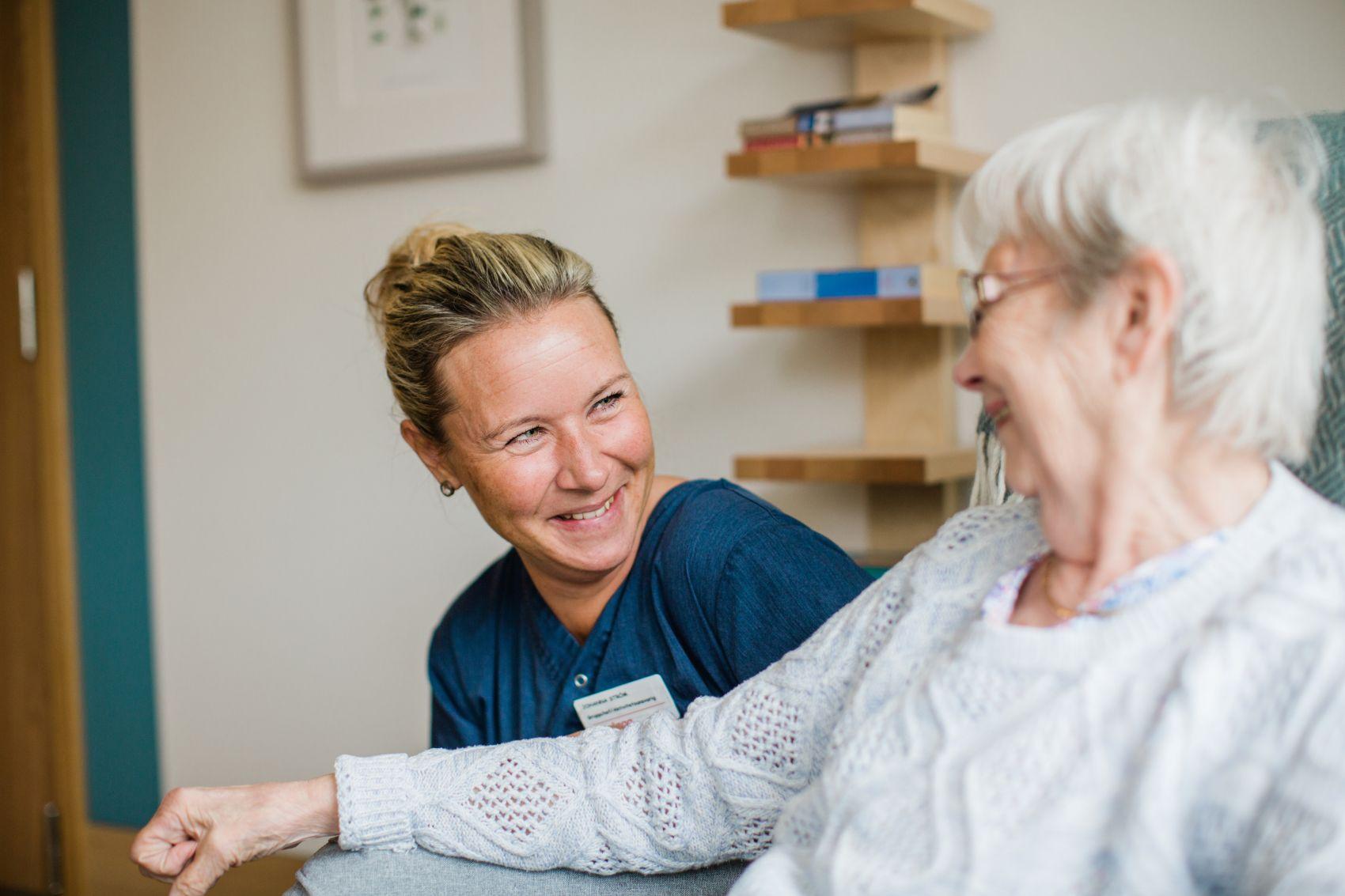 En helsemedarbeider og en eldre kvinne ler og koser seg på Kantarellen Bo- og rehabiliteringssenter.