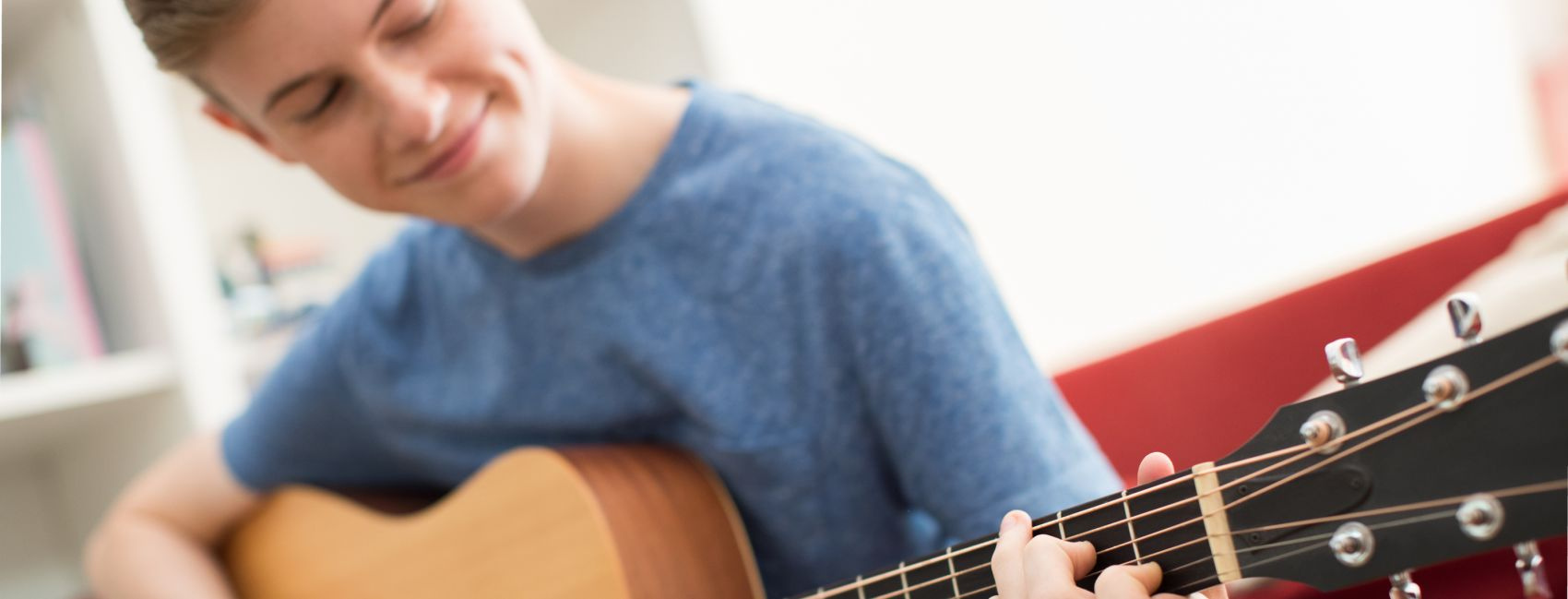 Ung gutt lærer seg å spille gitar gjennom musikkterapi hos Stenid.
