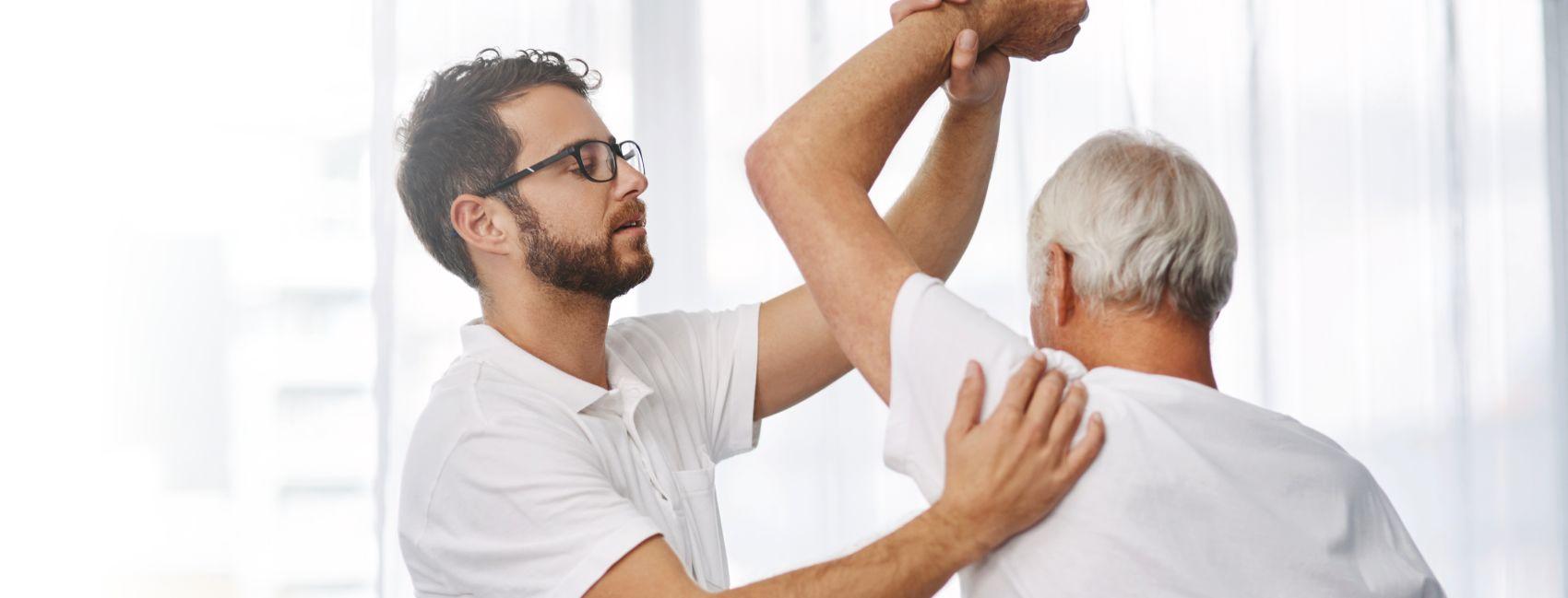 En mannlig fysioterapeut tøyer på skulderen til en eldre mann, som bor i Gabels Park.