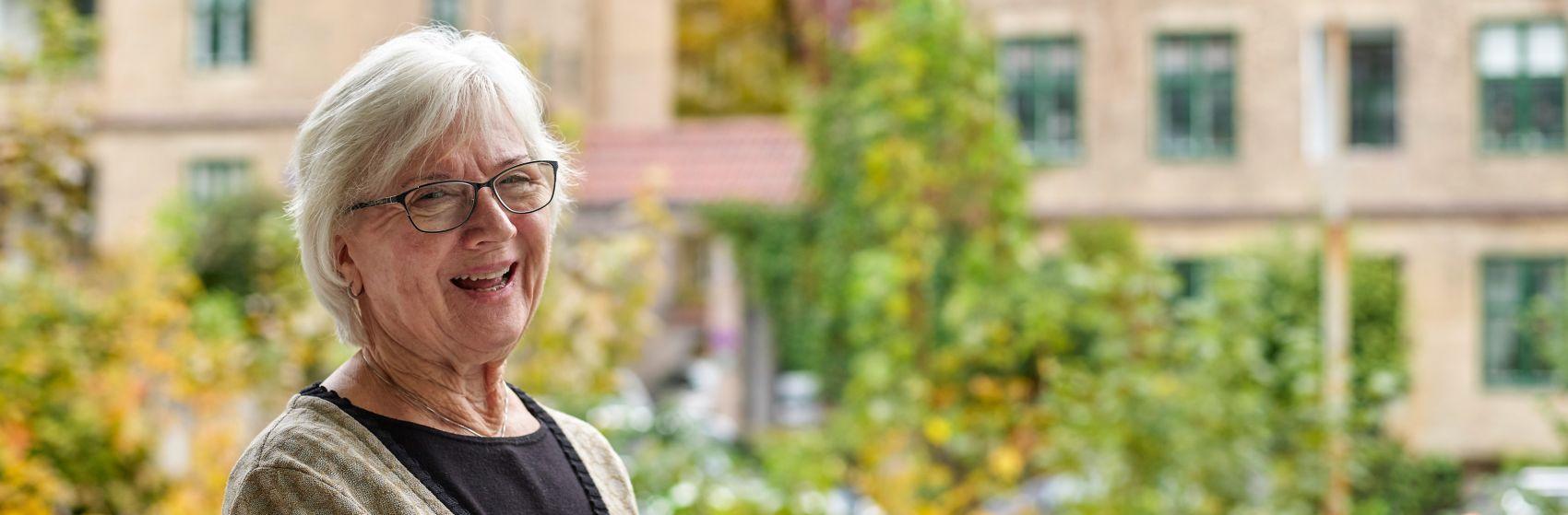 En eldre kvinne smiler til kameraet, hun står utenfor inngangen til Gabels Park.