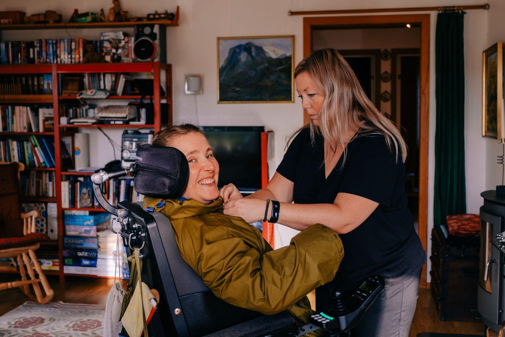 BPA-kunde Mari Bjurgren tar på seg jakken med bistand fra Stendi Assistanses assistent