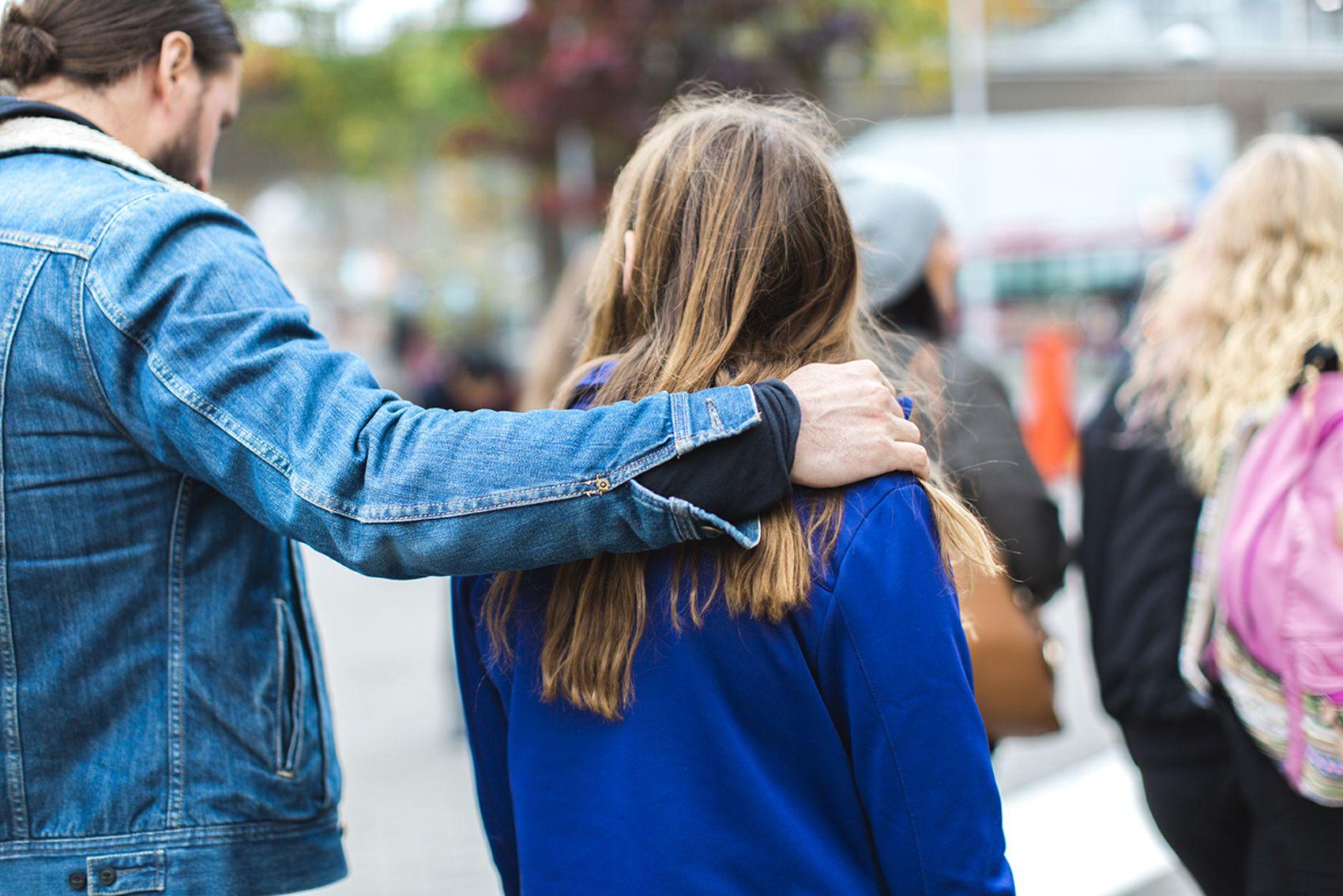 En voksen mann holder trygt, rundt skulderen til ei ung jente.