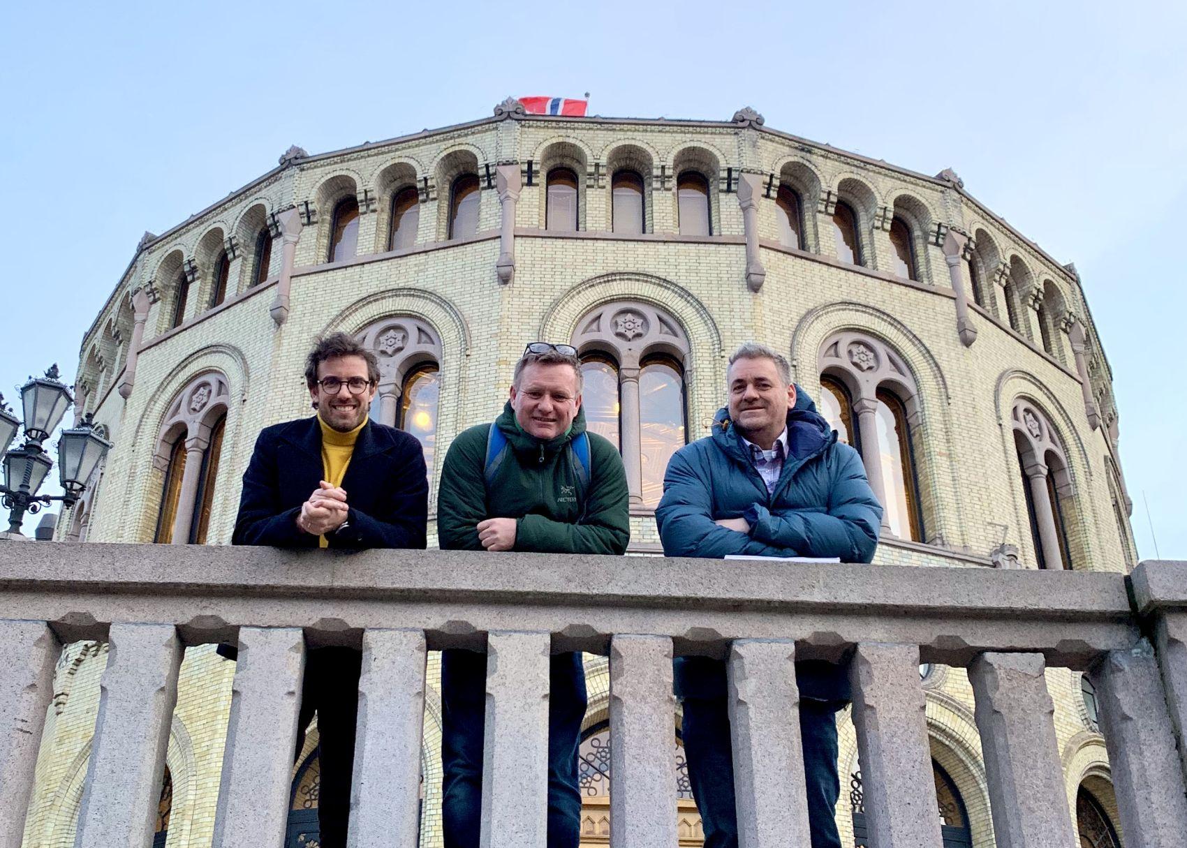 Tre menn fra Stendi poserer foran Stortinget