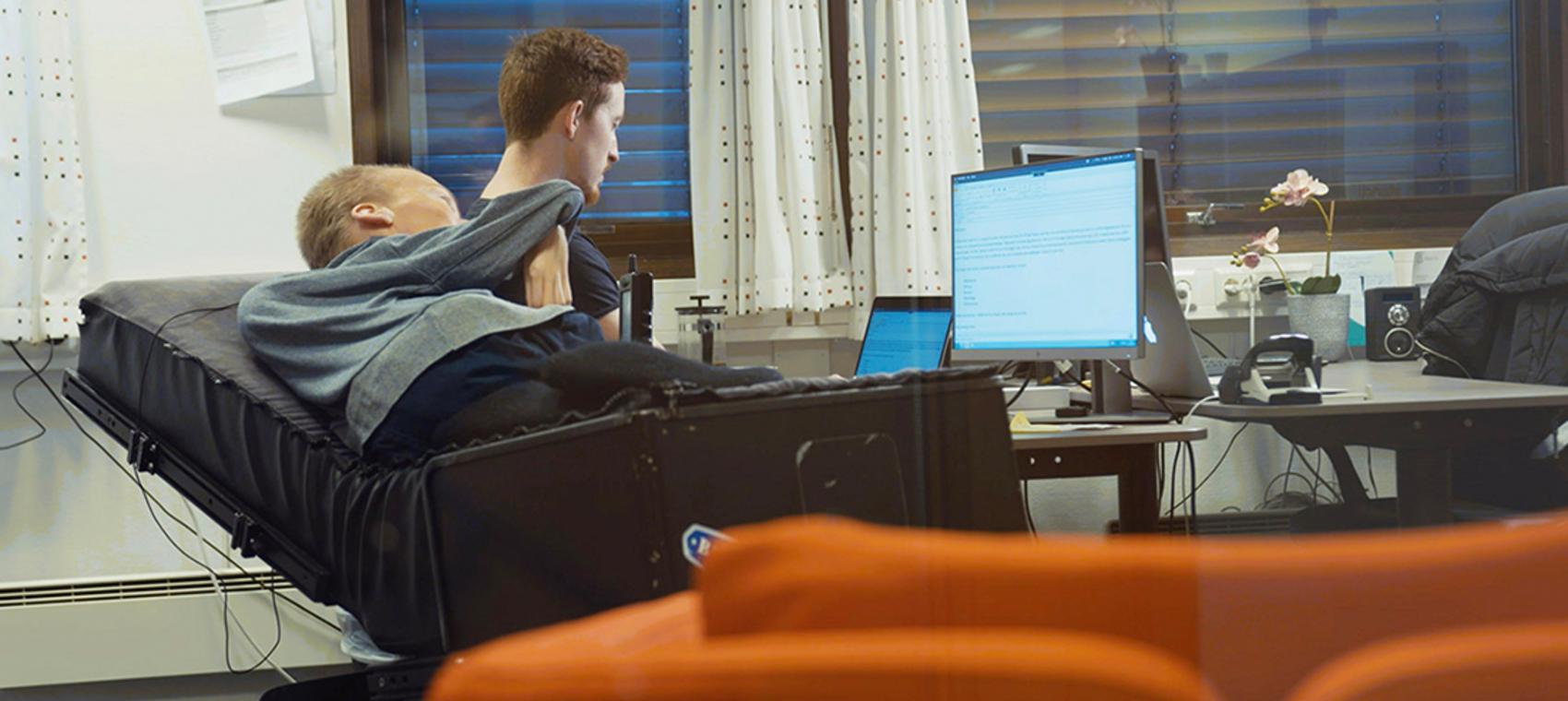 Torstein Lerhol som ligger i rullestol, får hjelp av assistenten sin fra stendi til å skrive på PC.
