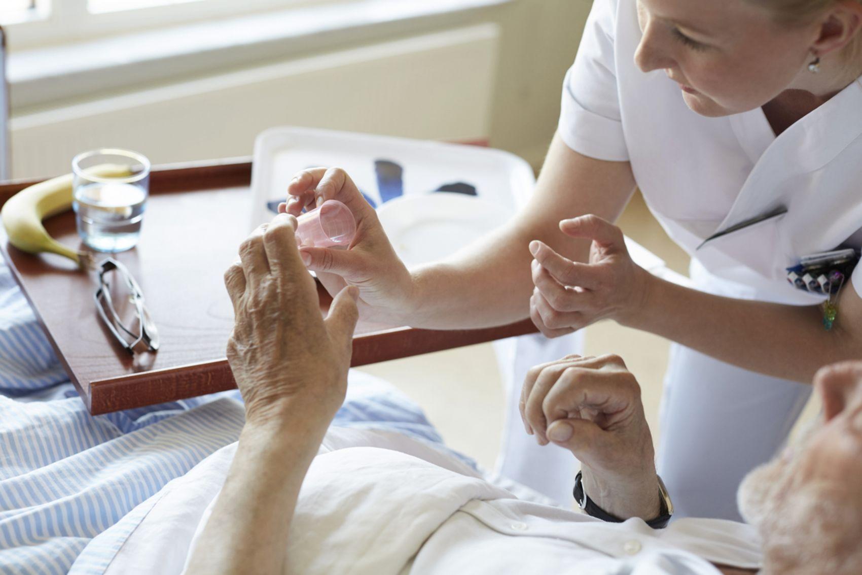 Helsefagarbeider fra Stendi gir medisiner til eldre mann.