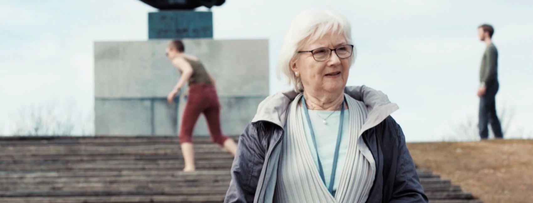 En senior kvinne på gåtur i Vigelandsparken, med Stendi trygghetsalarm rundt halsen.