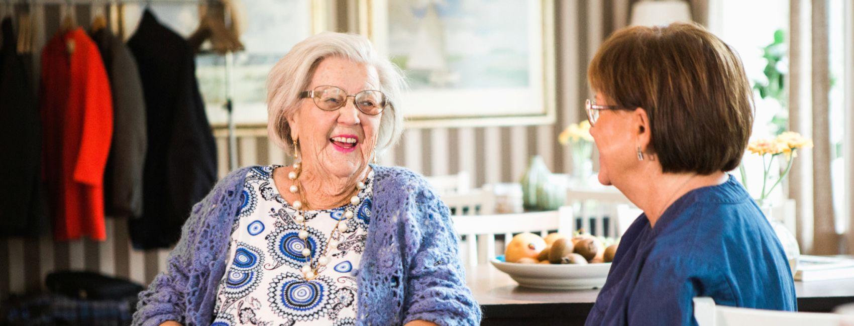 En eldre kvinne og en medarbeider sitter ved bordet og snakker på Stendis avdeling Omsorg+ på Ljabrubakken.