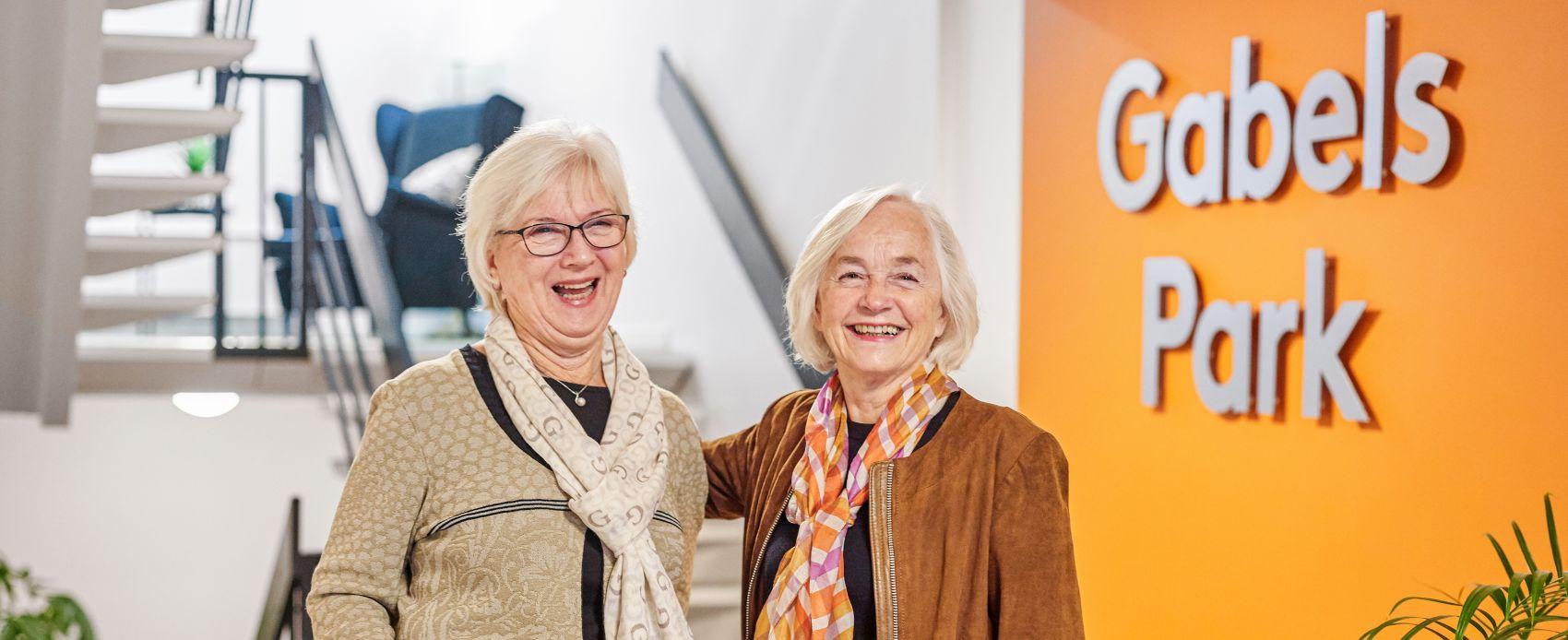 To eldre kvinner bosatt i seniorboligen Gabels Park smiler mot kamera. Foto
