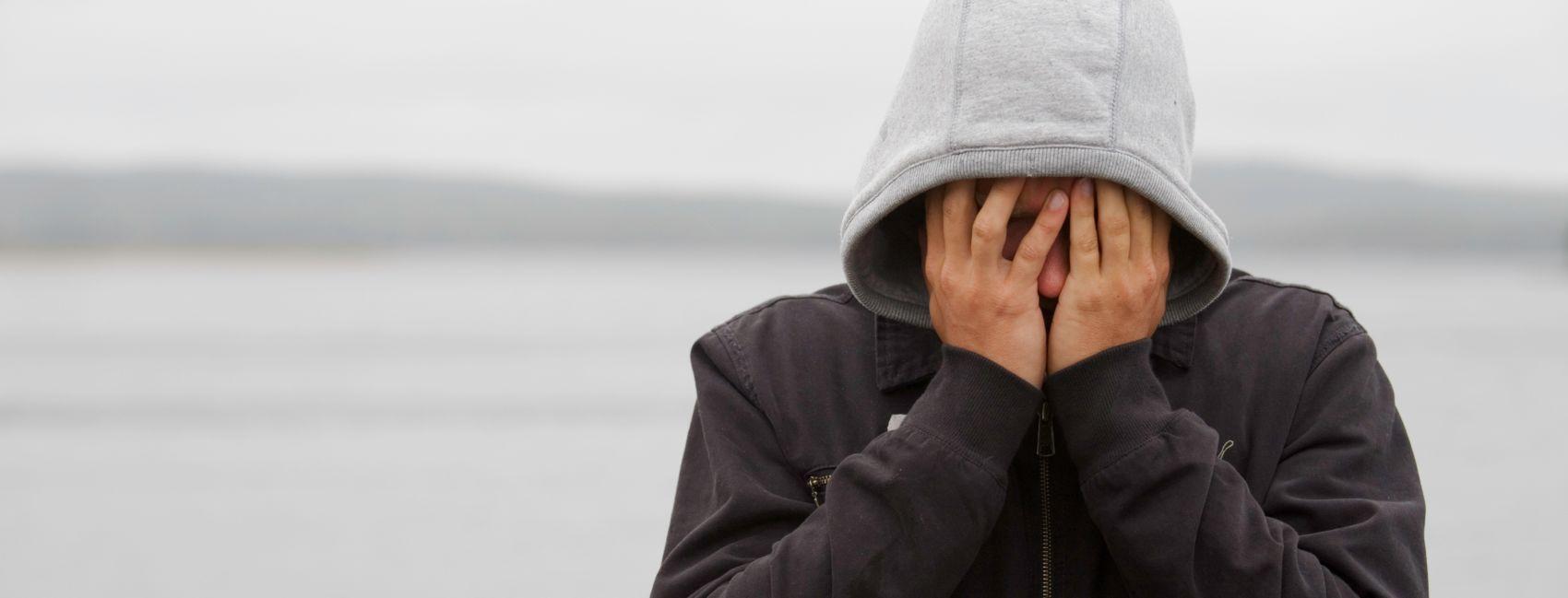 Gutt som dekker ansiktet med hendene sine.