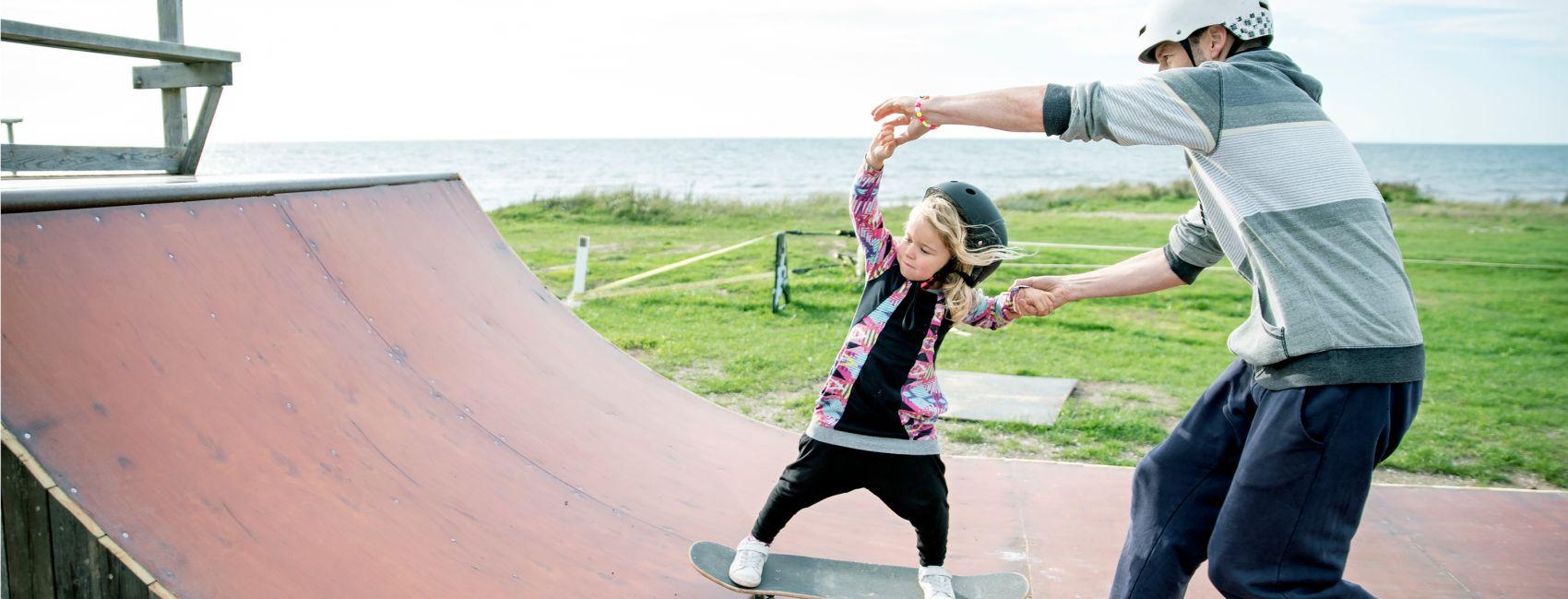 Fosterfar lærer fosterbarnet sitt, en liten jente å stå på skateboard
