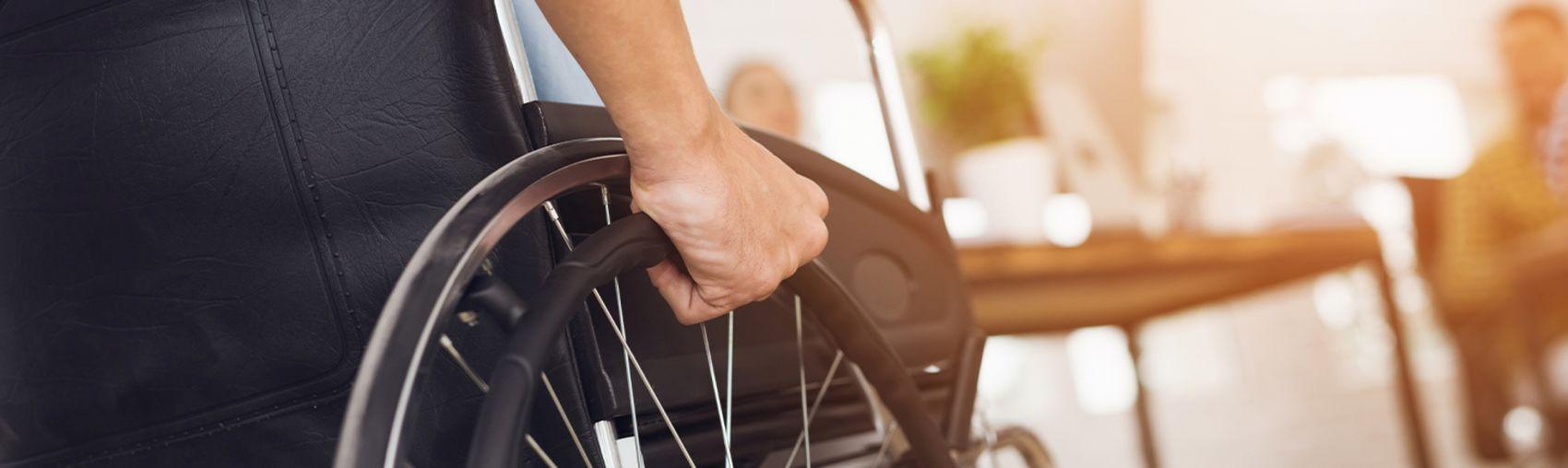 En mann i rullestol har hånden sin på det ene hjulet