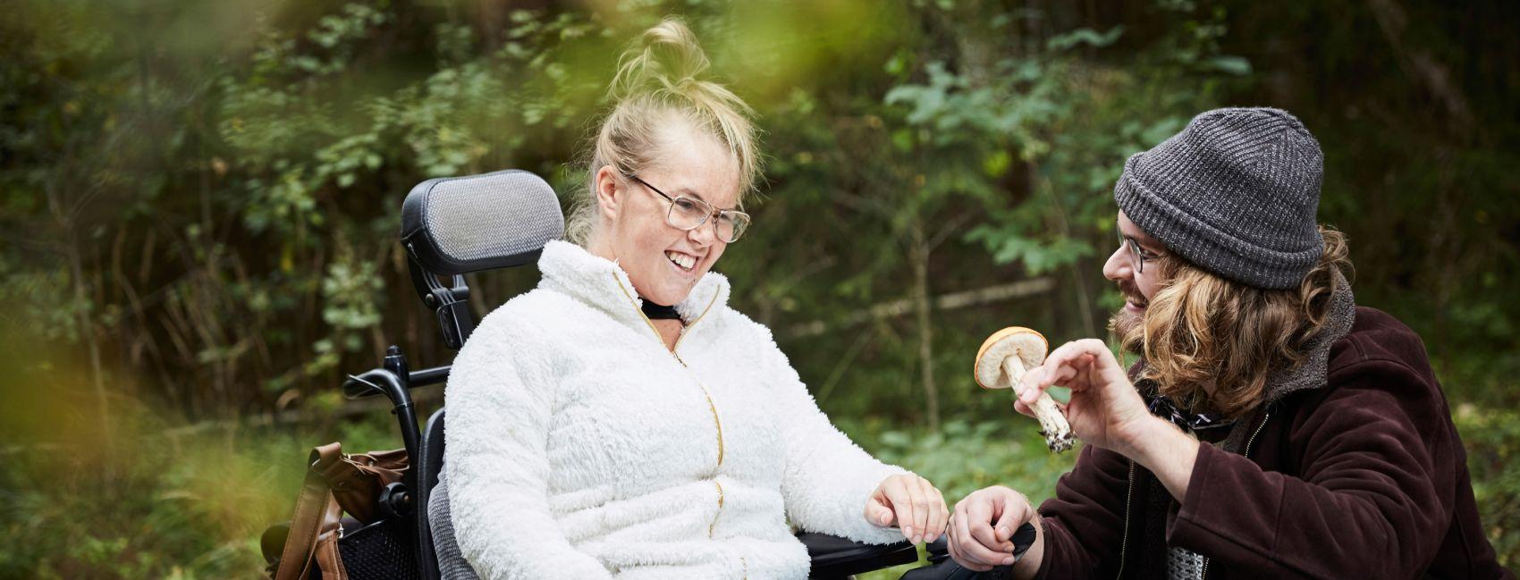 Stendi assistent som bistår ung kvinne med funksjonsnedsettelse