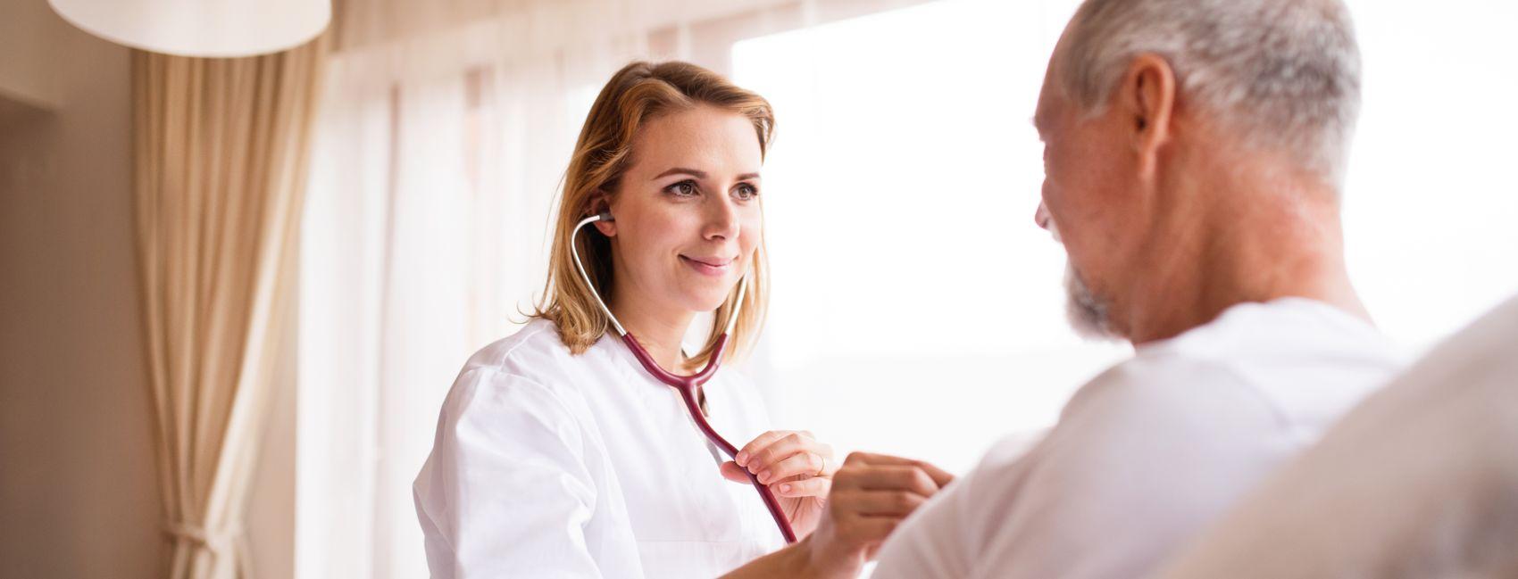 En hjemmesykepleier fra Stendi, lytter på en manns bryst med stetoskop.