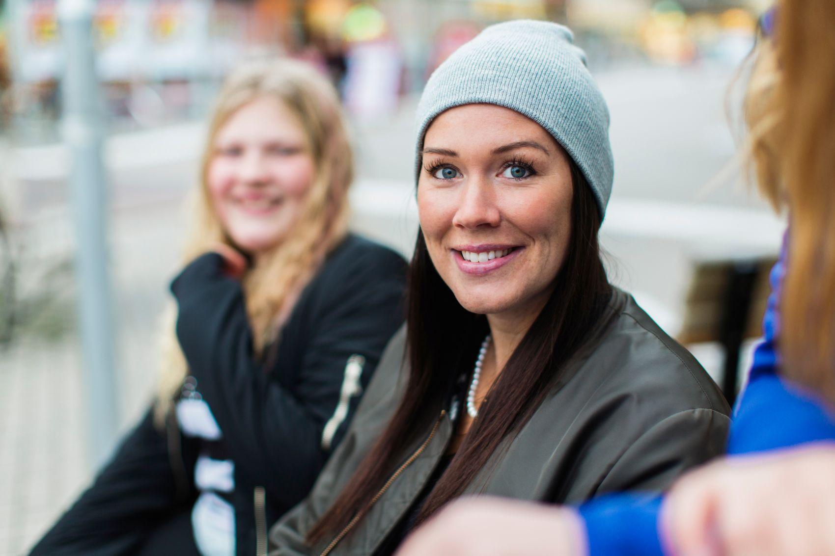 En smilende kvinne, i bakgrunn sitter en tenåringsjente