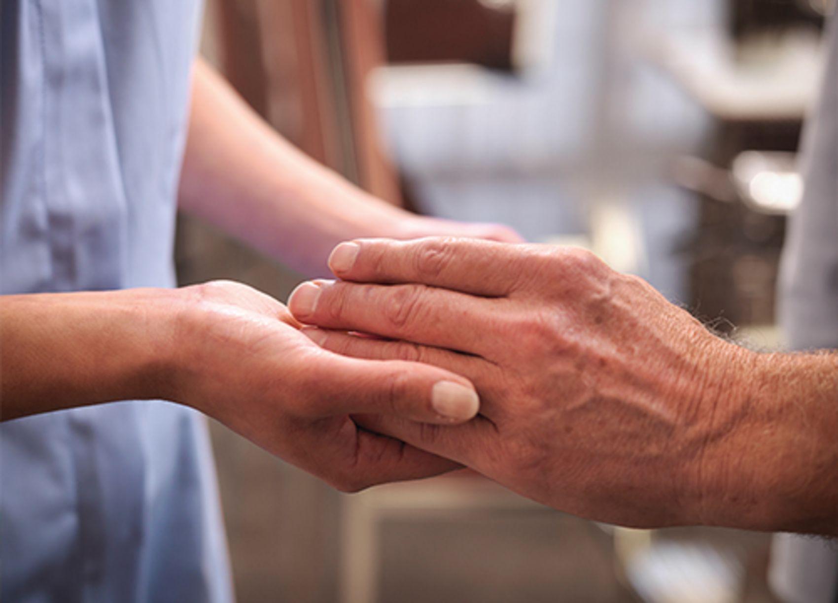 Det trengs flere varme hender i omsorgen i framtiden. En pleier holder i hendene til en eldre mann.