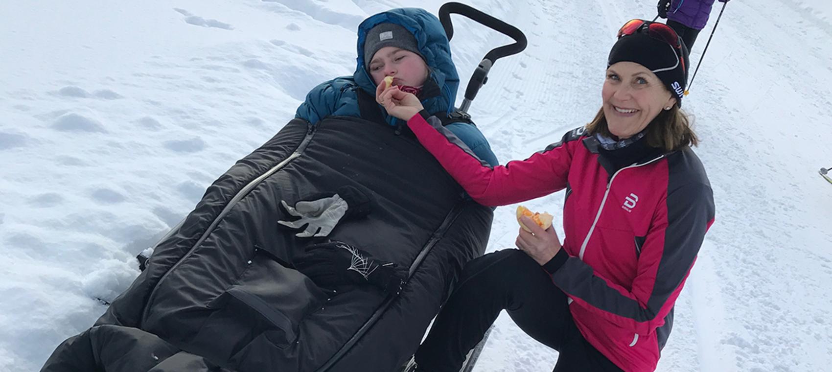 Funksjonhemmed ung jente ligger i en pulk i skisporet, ved siden av sitter moren.