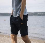 Mens Vipe Shorts i fargen Sky Captain/Vintage Indigo fra Tufte Wear. Bildet viser shortsen på herremodell som går langs stranden