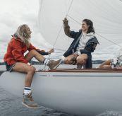 Drifter Jacket fra Amundsen Sports til dame. Bildet viser rød, hvit og blå jakke på kvinner ombord på seilbåt i hyggelig prat