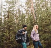 Verglas Tur Pant fra Helly Hansen. Bildet viser en kvinne og en mann med turtøy på i skogen.