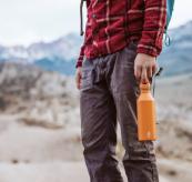 Drikkeflaske fra Mizu M8 i fargen burnt orange. Bildet viser en mann på tur, som holder flasken i hånden