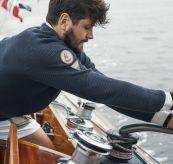 Drifter Sweater til herre fra Amundsen Sports i fargen blue surf. Bildet viser genseren på mann ombord på båt