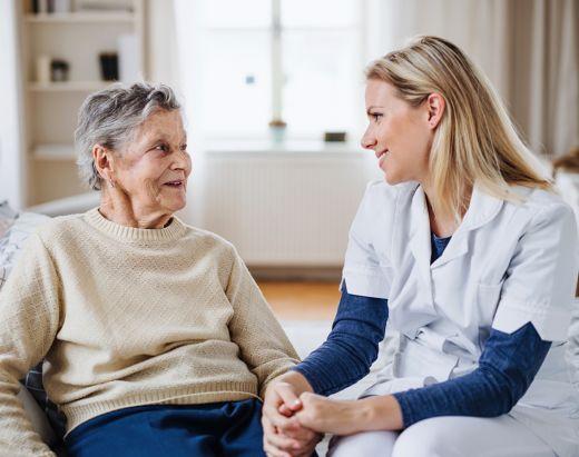 En eldre kvinne og en hjemmesykepleier fra Stendi holder hender, og har en hyggelig prat.