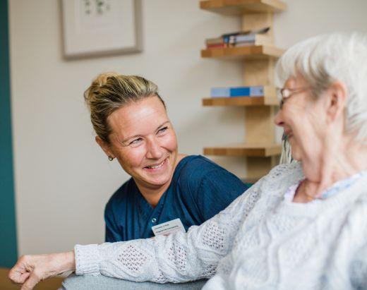 En sykepleier i Stendi snakker med en av en eldre dame ved et av våre sykehjem.
