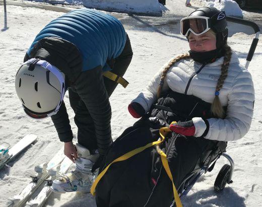 En funksjonshemmed jente får hjelp av en assistent fra stendi i skibakken