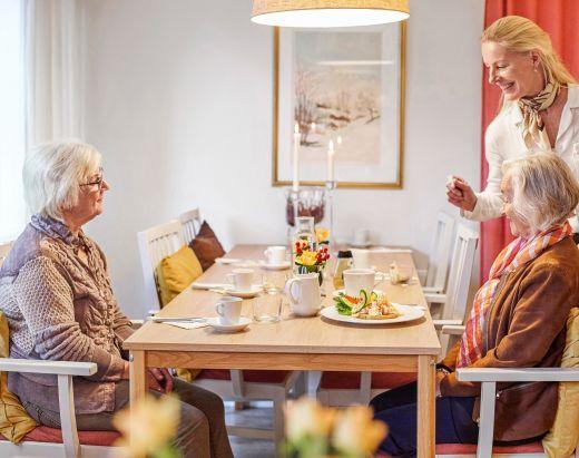 Husvertinnen i Gabels Park snakker med to eldre kvinner ved bordet i restauranten Det Glade bord.