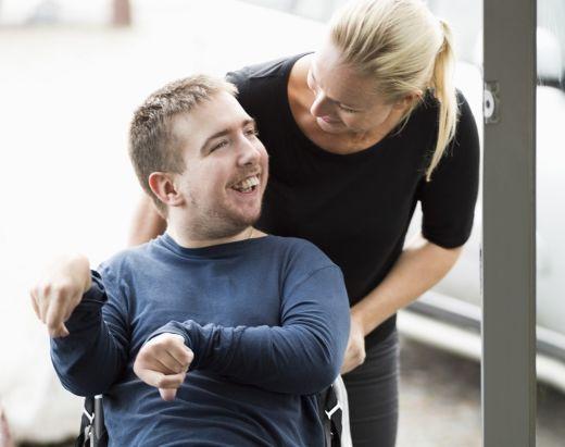 ung mann i rullestol ler og prater med assistenten sin fra Stendi