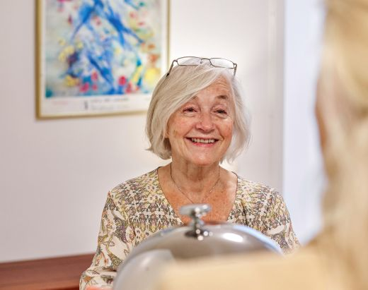 En glad eldre kvinne får servert middag i Gabels Park.