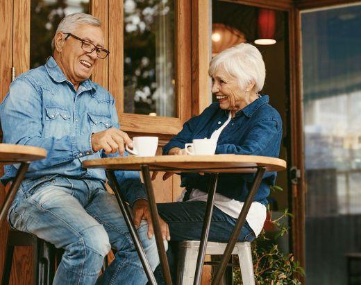 To seniorer, en mann og en kvinne, nyter en kopp kaffe på en liten café i nærheten av Gabels Park.