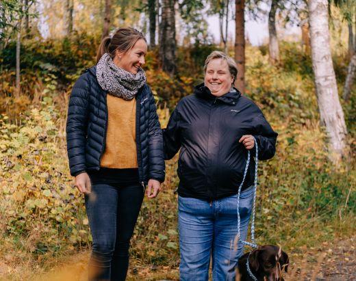 BPA-kunde på tur i skogen med hund og assistent fra Stendi Assistanse