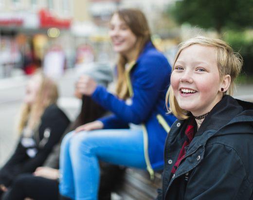 En tenåringsjente som bor i fosterhjem smiler bredt.