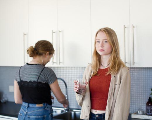 To tenåringsjenter på et kjøkken, tar seg et glass vann