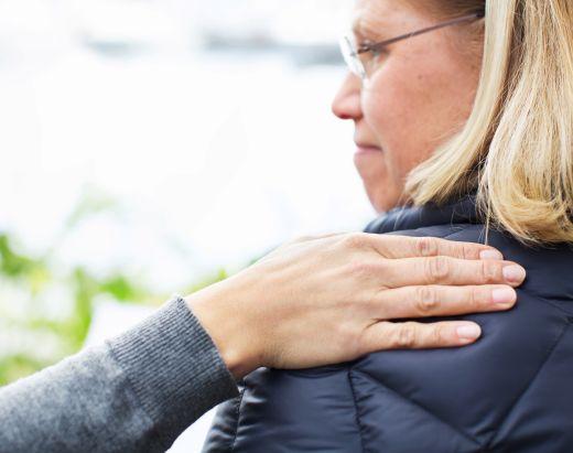 En miljøarbeider i Stendi legger en trøstende hånd på skulderen til en kvinne.