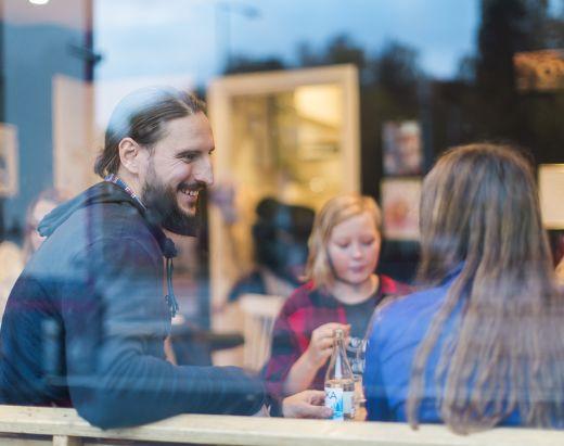 En fosterfar via Stendi Barnevern sitter på kafe sammen med to tenåringsjenter.