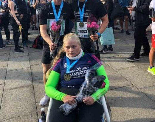 Jente i rullestol poserer sammen med assistentene sine fra Stendi BPA.