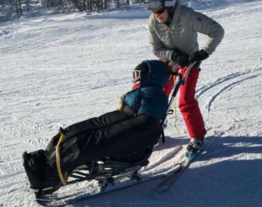 Funksjonshemmed ung jente får hjelp ned skibakken.