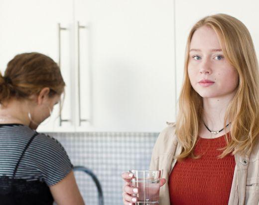En jente står med ryggen til ved vasken, og en jente står med et glass vann i hånden.