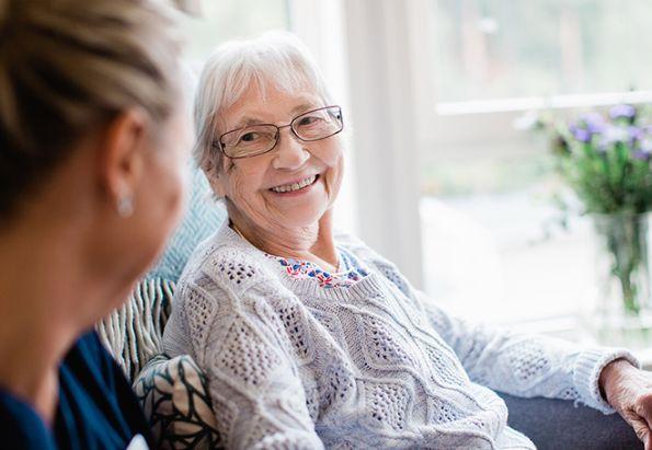 En hjemmesykepleier fra stendi er på hjemmebesøk hos en eldre kvinne, de smiler og hygger seg.