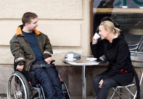 Ung mann i rullestol drikker kaffe sammen med assistenten sin fra Stendi