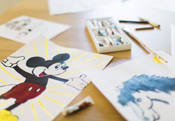 Et malerie av Mikke mus ligger på et bord med andre malerier, maling og pensler