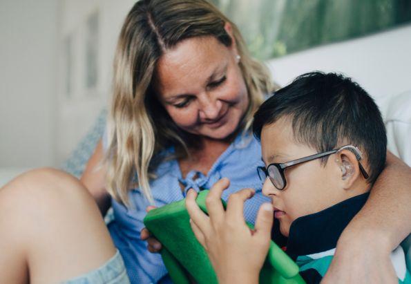 En mor holder rundt sønnen sin som har downs syndrom, de ser på et nettbrett sammen